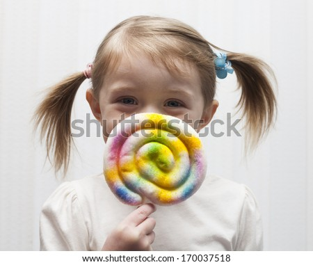 Beautiful little girl holding a big colorful lollipop - stock photo