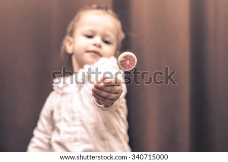 Beautiful little girl holding a small watermelon lollipop.  - stock photo