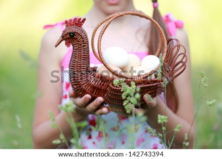 Beautiful little girl holding basket of raw eggs/Cute young girl standing in the tall grass outdoors - stock photo