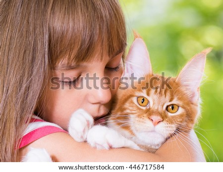 Beautiful little girl holding cute red Maine Coon kitten. Cat looking at camera. - stock photo