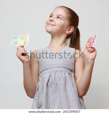 Beautiful little girl holding euro cash banknotes