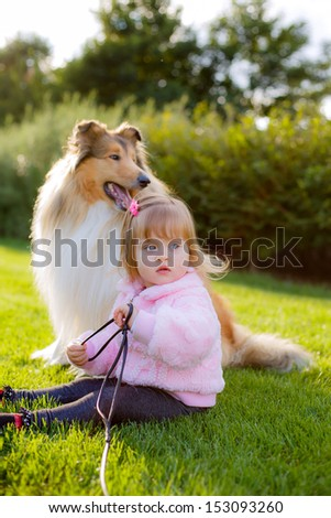 beautiful little girl holding the leash dog Collie