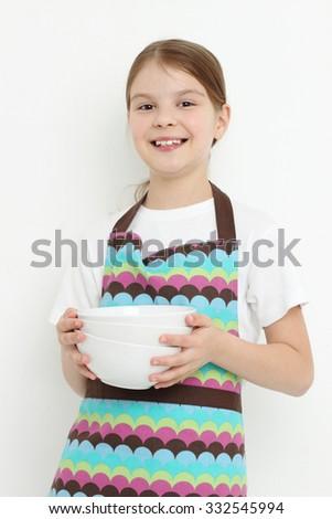 Beautiful little girl holding white bowls - stock photo