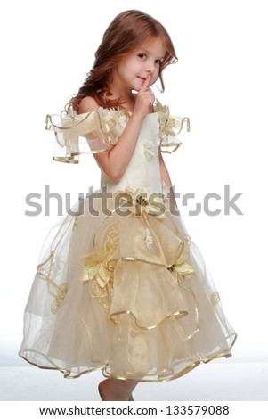 Beautiful little girl in a beautiful dress on a white background