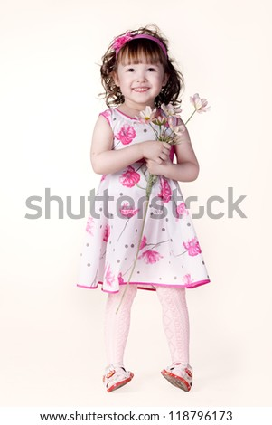 beautiful little girl in a dress with a flower in your hand