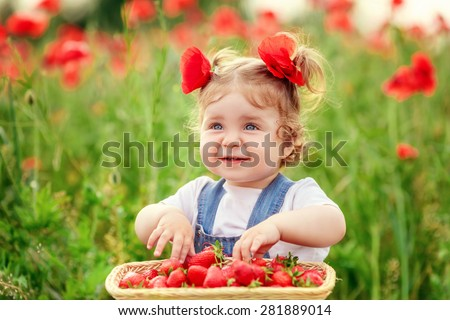 beautiful little girl in a field of poppies with strawberries - stock photo