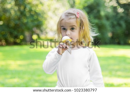 Beautiful little girl in a park on a picnic with ice cream. Spring sunny concept. Happy mothers day. Toddler.