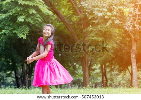 Beautiful little girl in a pink dress posing on the grass.in sunlight / Asian girl standing in the park