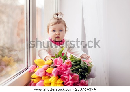 beautiful little girl in a pink dress with a bouquet of tulips. March 8 Mother's Day - stock photo