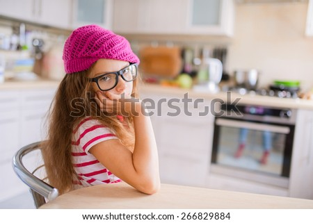 Beautiful little girl in a red cap sits at a table in the kitchen and thinking. - stock photo