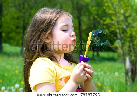Beautiful little girl in a summer meadow - stock photo