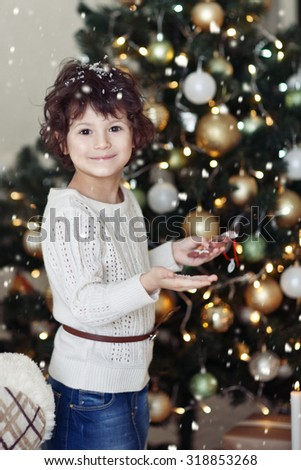 Beautiful little girl in a white winter sweater sits in the bed at Christmas trees and hugging a teddy bear. gift for New Year  - stock photo