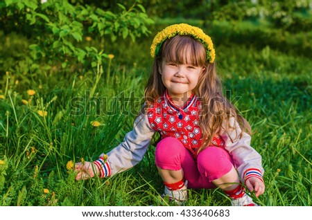 Beautiful little girl in a wreath from dandelions and picking flowers in the summer Park