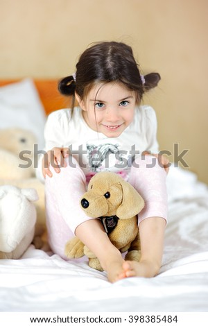 beautiful little girl in bed with toys