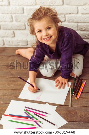 Beautiful little girl in casual clothes is drawing using colorful pencils, looking at camera and smiling, sitting against white brick wall - stock photo