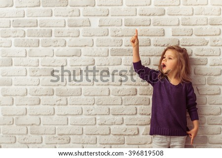 Beautiful little girl in casual clothes is pointing up and looking away, standing against white brick wall - stock photo