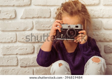 Beautiful little girl in casual clothes is taking a photo using a camera, looking at camera and smiling, sitting against white brick wall - stock photo