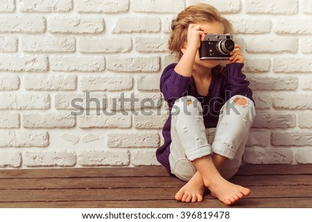 Beautiful little girl in casual clothes is taking a photo using a camera, sitting against white brick wall - stock photo