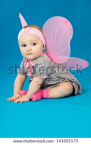 beautiful little girl in costume at a blue background