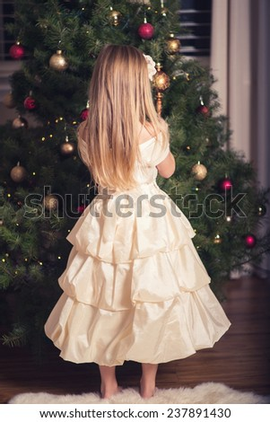 Beautiful little girl in dress decorating Christmas Tree.Rear view. - stock photo