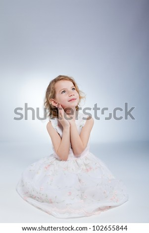 beautiful little girl in dress think, dream looking up, portrait of cute adorable princess sitting on floor on grey background - stock photo