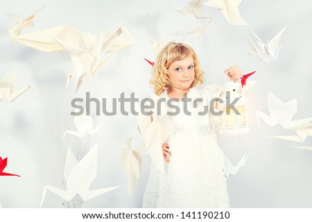 Beautiful little girl in her dream world surrounded with paper birds, holding a lamp. - stock photo