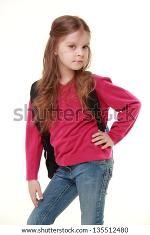 Beautiful little girl in jeans and a sweater holding a school bag on a white background