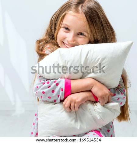 beautiful little girl in pajamas with a pillow in his hands - stock photo