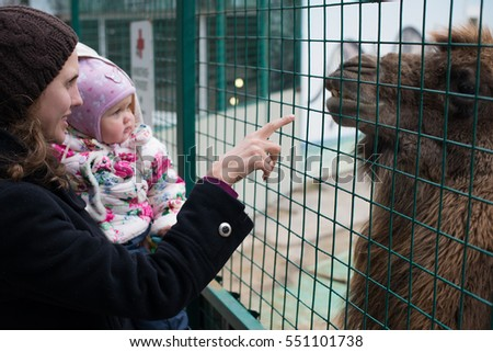 Beautiful little girl in pink coat feeding humped camel.