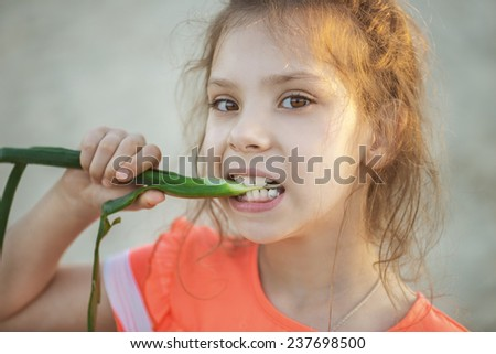 Beautiful little girl in pink dress eats green feather bow.