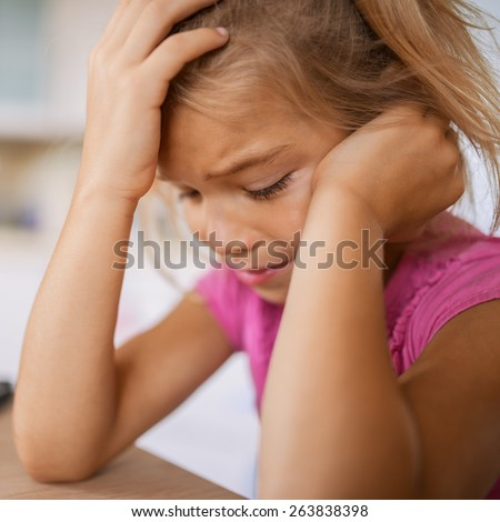 Beautiful little girl in pink dress sits at table and cries. - stock photo
