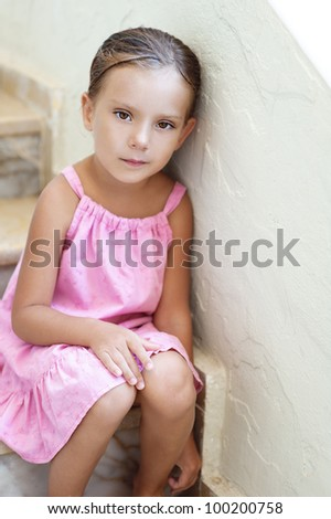 Beautiful little girl in pink dress sitting on stone steps of ladder. - stock photo
