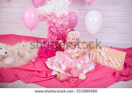 Beautiful little girl in pink dress with sweet cakes