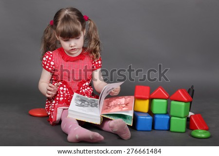 Beautiful little girl in red dress sits on floor and reads book near toys in grey studio - stock photo