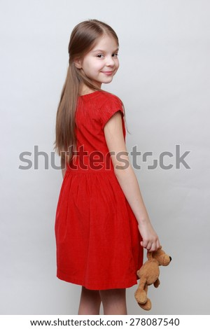 Beautiful little girl in red fashion dress holding lovely toy teddy bear - stock photo