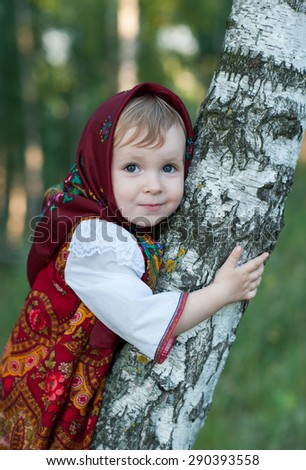 Beautiful little girl in russian traditional clothes in nature.Little cute girl in Russian national clothes.Traditional Russian folk costume.Portrait of a cute little girl outside
