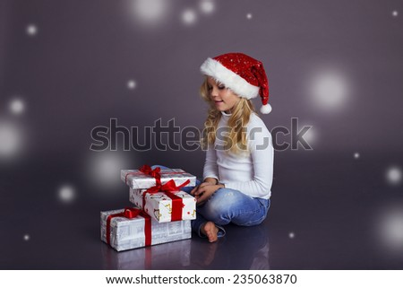 beautiful little girl in Santa hat and jeans smiling and holding a box with Christmas presents - stock photo
