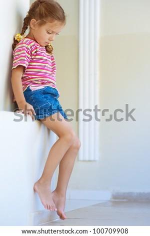 Beautiful little girl in shorts sitting on stone ledge, and sad. - stock photo