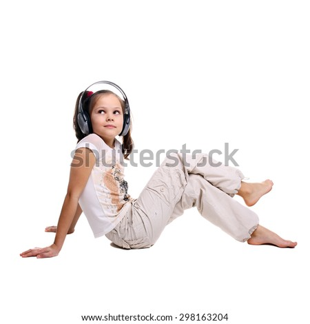 beautiful little girl in the headphones sitting on the floor