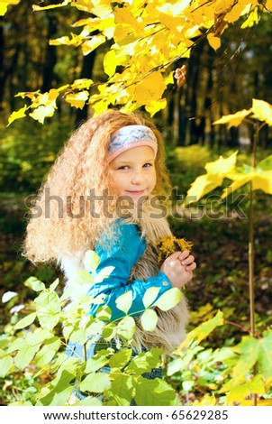 beautiful little girl in the rays of a bright sun at autumn