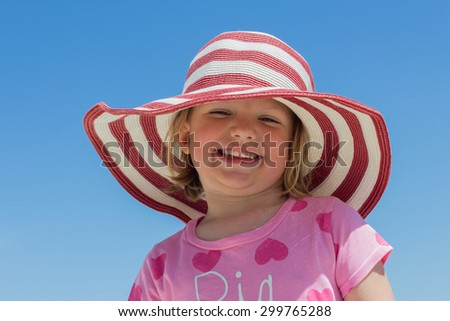 Beautiful little girl in the striped hat on the beach.