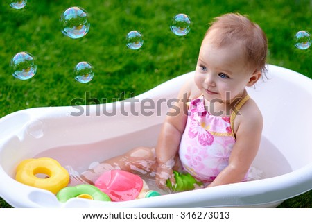 beautiful little girl in the summer bathing with soap bubbles.