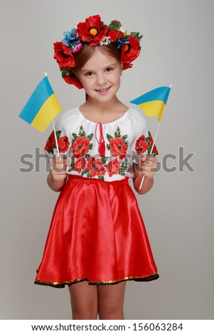 Beautiful little girl in the Ukrainian national costume holding a small Ukrainian flag on a gray background on Holiday