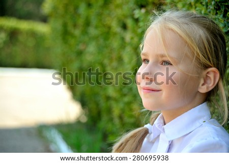 Beautiful little girl in white blouse close-up in profile, on green background of summer city park. - stock photo