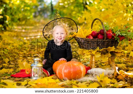 Beautiful little girl in witch costume on a picnic, on Halloween in autumn park, smiling. Halloween. National holidays and traditions.