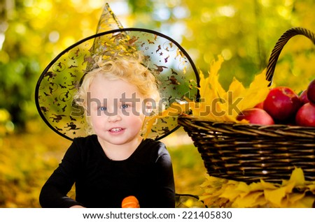 Beautiful little girl in witch costume on Halloween in autumn park with a basket of apples. Halloween. National holidays and traditions.  - stock photo