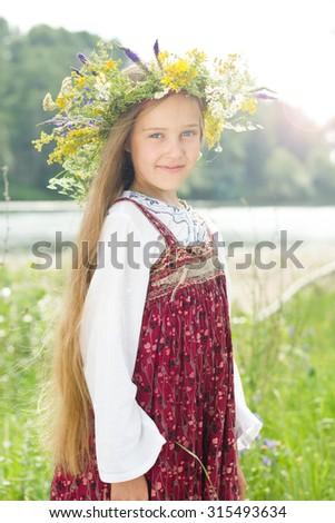 Beautiful little girl in wreath of flowers in meadow - stock photo
