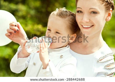 Beautiful little girl is drinking water on the hands of her mother in a park a sunny summer day. - stock photo