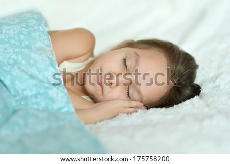 Beautiful little girl is sleeping in her bed at home - stock photo