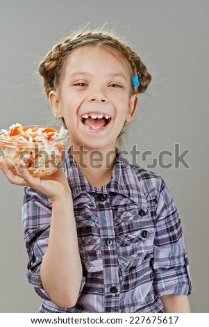 Beautiful little girl laughing and holding salad, on gray background.